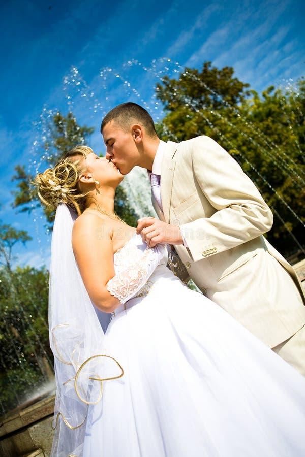 De jonggehuwden kussen stock foto