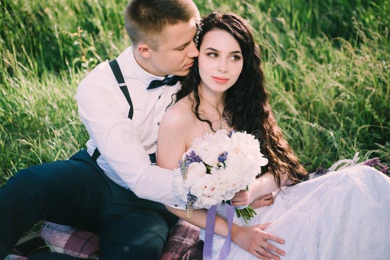 De jonggehuwden in liefde zitten op het gras in het park de bruid en de bruidegom glimlachen en hebben pret bij de huwelijkspickn stock afbeelding