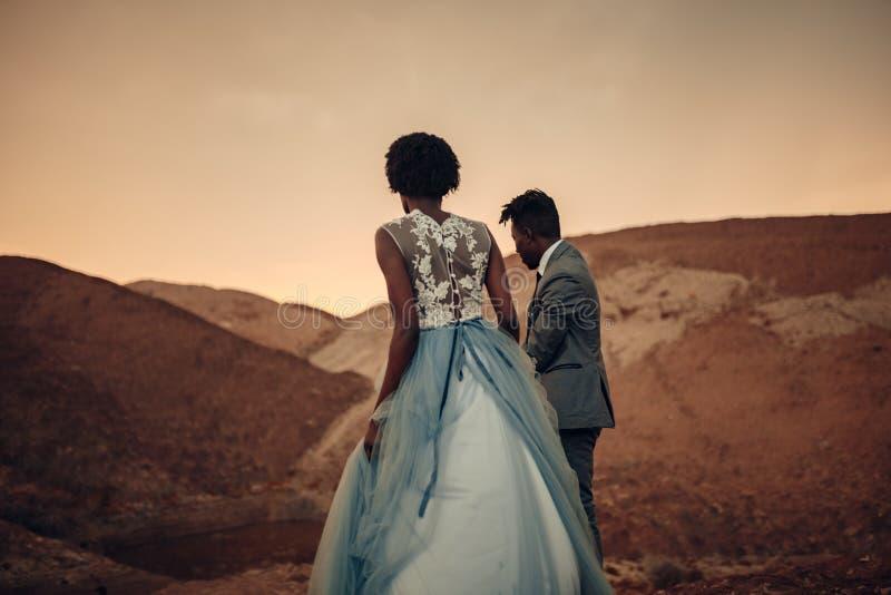 De jonggehuwden lopen in canion bij zonsondergang stock foto