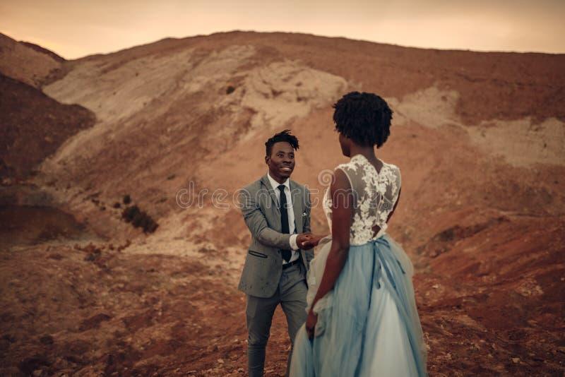De jonggehuwden lopen in canion bij zonsondergang royalty-vrije stock foto's