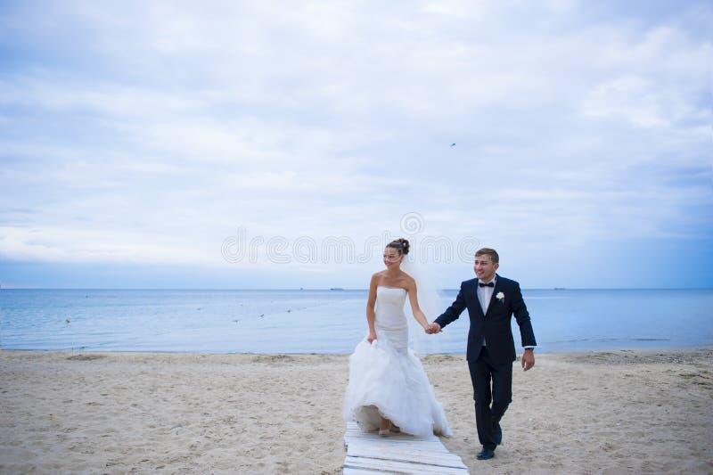 De jonggehuwden lopen op het strand royalty-vrije stock afbeeldingen