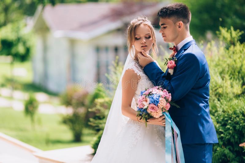 De jonggehuwden maakten ruzie en de man probeert om met de bruid te verzoenen Hij vraagt haar teder om te draaien De bruid is royalty-vrije stock fotografie