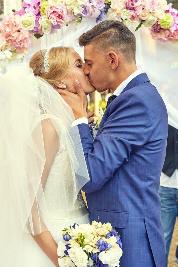 De jonggehuwden onder ceremonie overspannen in mooie de lentedag stock foto's