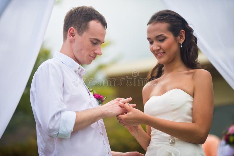 De jonggehuwden op huwelijk dragen elke trouwringen stock foto