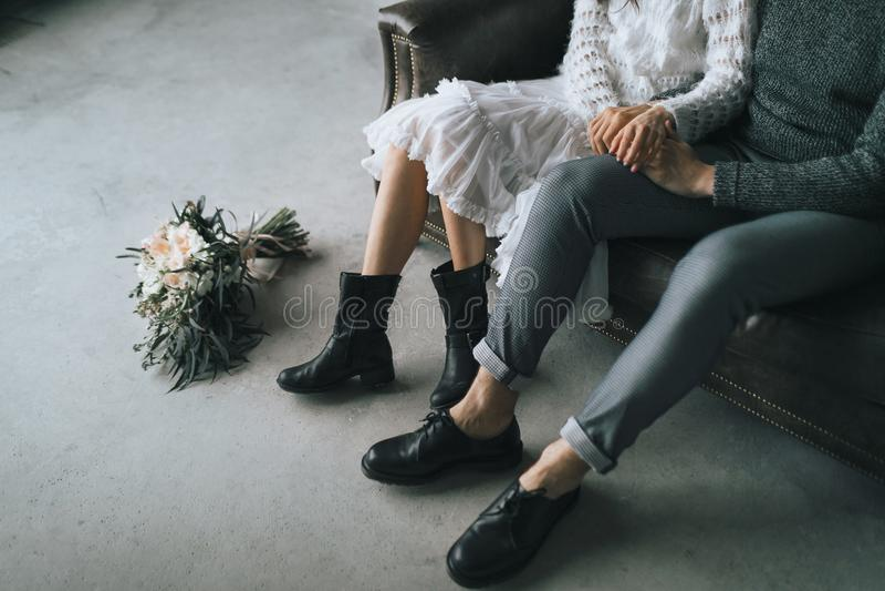 De jonggehuwden zitten thuis op de bank Benen in toevallige laarzen van jong paar stock afbeelding