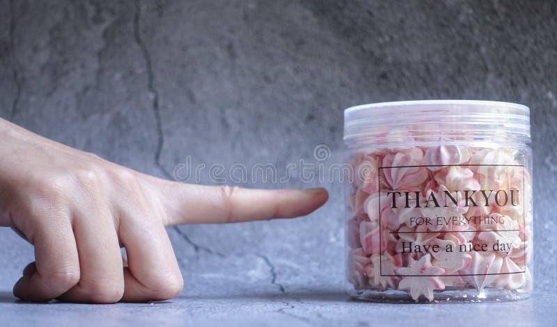 De juiste Persoon 's het Punt van de Dinger van de Index die Duidelijke Plastic container aanwijst die op Grijs Oppervlak wo royalty-vrije stock afbeelding