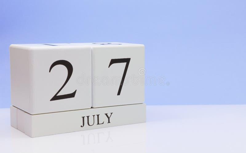 27 de julho dia 27 do mês, calendário diário na tabela branca com reflexão, com claro - fundo azul Horas de verão, espaço vazio imagem de stock