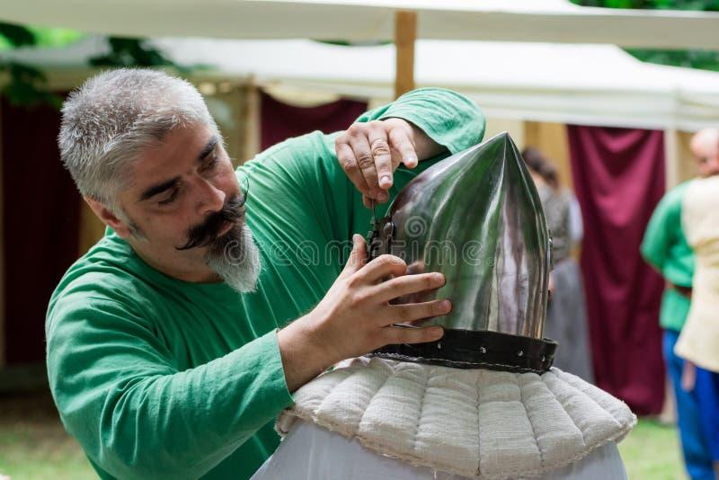 15 de julio de 2017 Ploiesti Rumania, festival medieval - cerrajero que repara el casco de la armadura fotografía de archivo