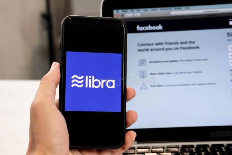 18 de junio de 2019, Ljubljana Eslovenia - la mano que sostenía un smartphone con el logotipo del libra en ella, al lado de la pá foto de archivo