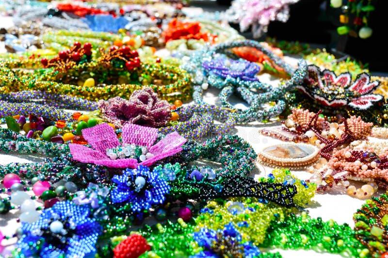 De juwelen van verkopende mooie kleurrijke vrouwen van parels Eerlijk - een tentoonstelling van volksvaklieden royalty-vrije stock afbeelding