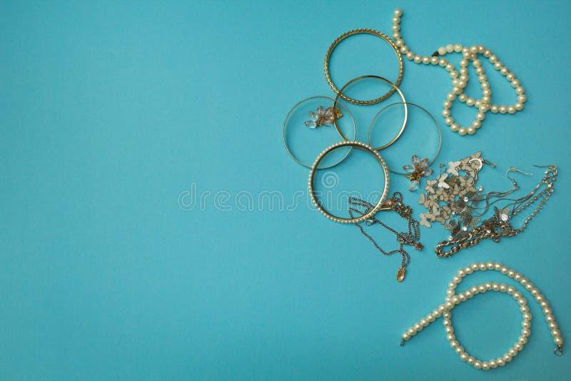 De juwelen van vrouwen en ander materiaal op een blauwe achtergrond royalty-vrije stock fotografie