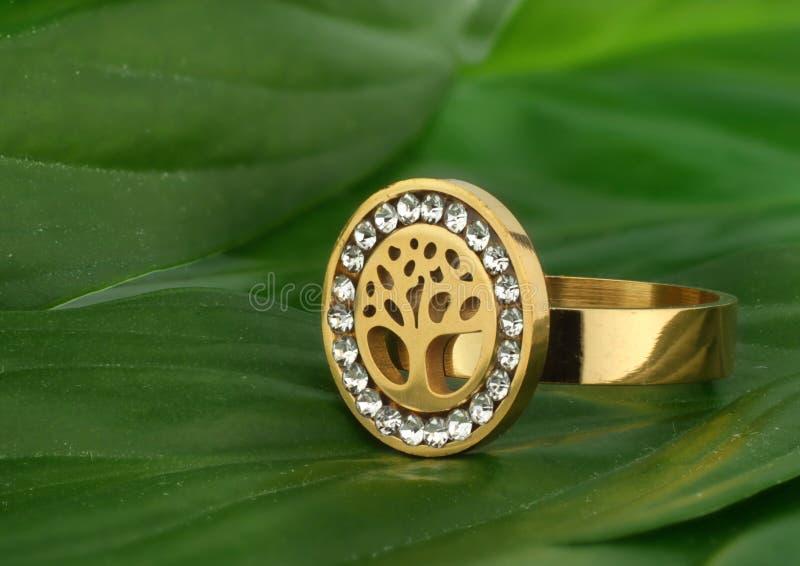 De juwelenring met diamanten, vorm van boom, op groen doorbladert als achtergrond stock foto's