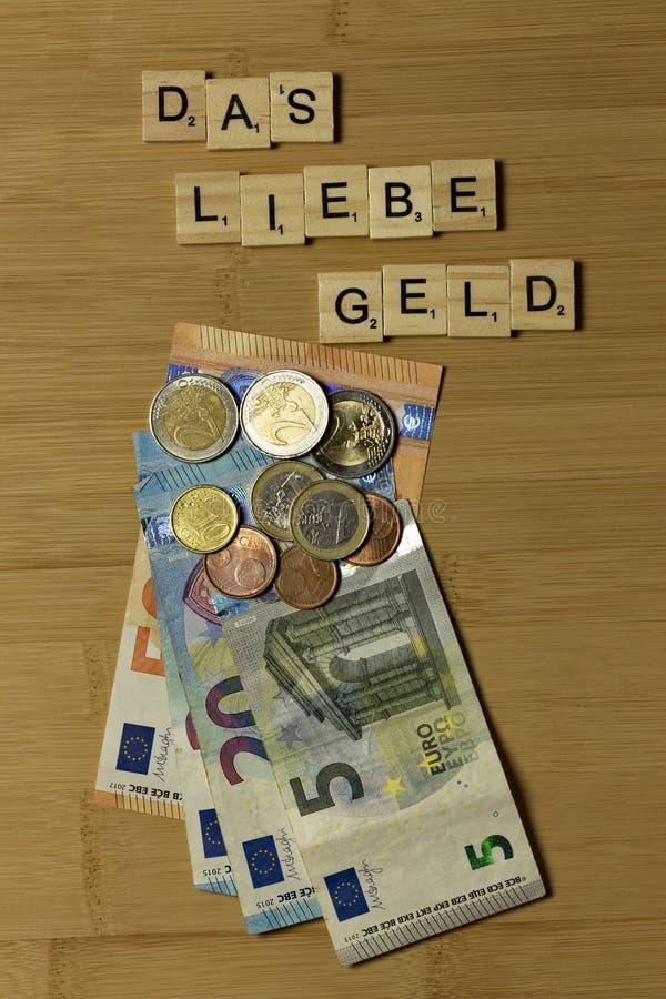 De kära pengarna, ord i tysk Das-liebe kastrerar royaltyfri bild
