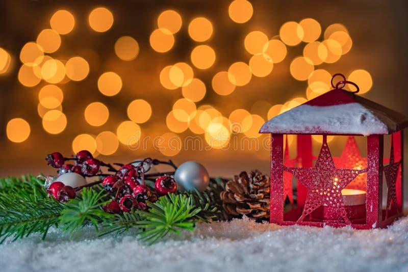 De kaars van de Kerstmislantaarn met decoratie over sneeuw en fonkelende lichtenachtergrond stock foto's