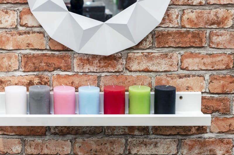 De kaarsen van verschillende kleuren zijn op de witte plank in het zolderbinnenland stock foto