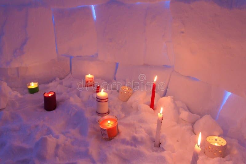 De kaarsen verlichten van binnenuit het huis van de iglosneeuw stock foto