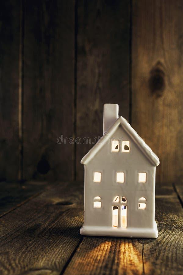 De kaarshouder van de wit huis gevormde keramiek op houten achtergrond stock fotografie