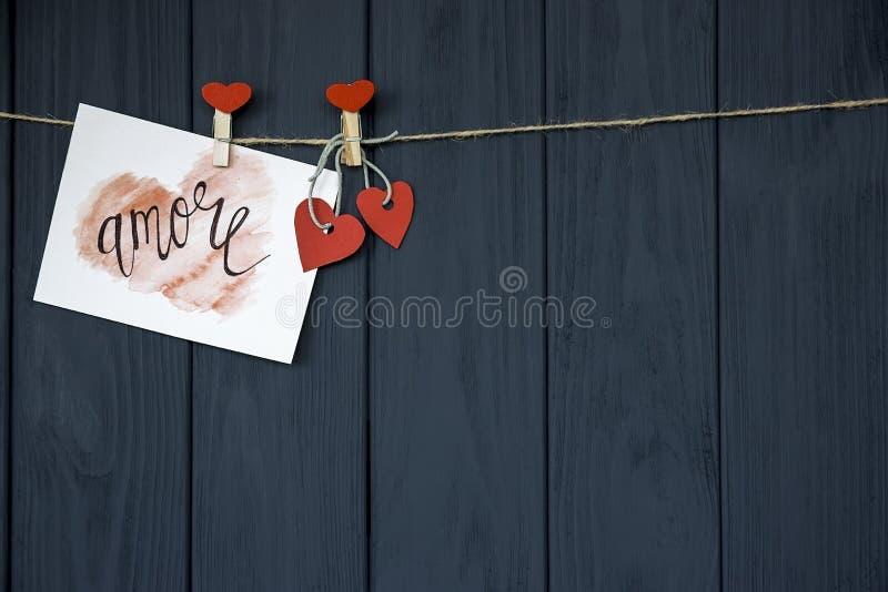De kaart` Amore ` natuurlijk koord van liefdevalentine ` s en rode spelden die op de rustieke achtergrond van de Drijfhouttextuur royalty-vrije stock fotografie