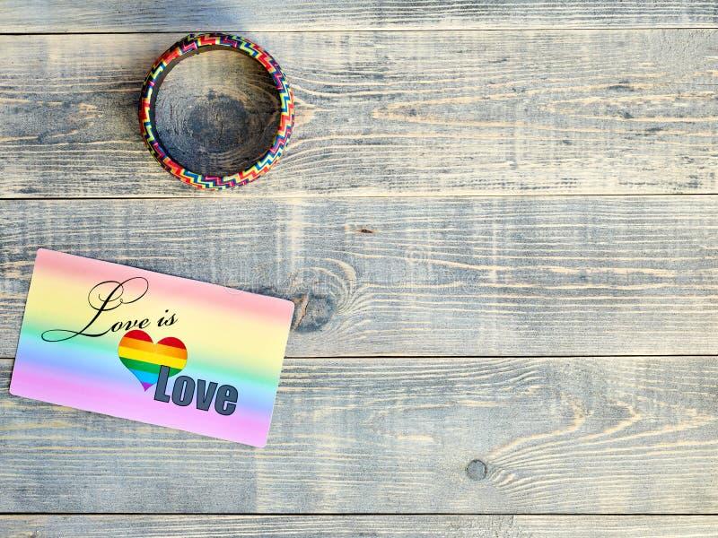 De kaart die liefde zegt is liefde met een regenboogachtergrond en een armband op hand met de LGBTQ-vlag LGBT ligt op lichtblauw royalty-vrije stock afbeeldingen
