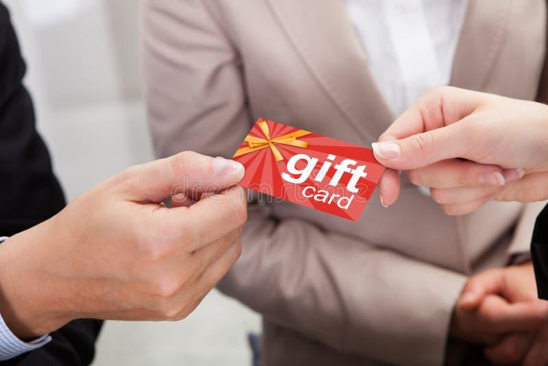 De Kaart van Businesspersonhands giving gift aan Andere Businessperson stock fotografie