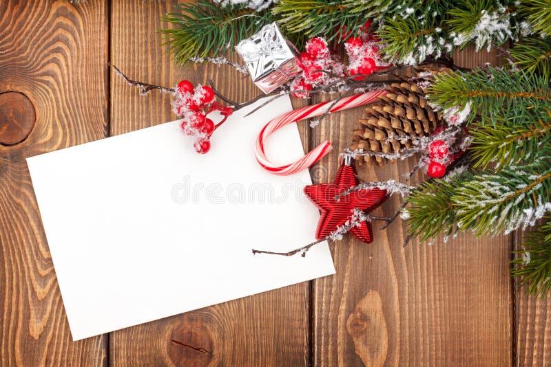 De kaart van de Kerstmisgroet of fotokader over houten lijst met Sn royalty-vrije stock afbeelding