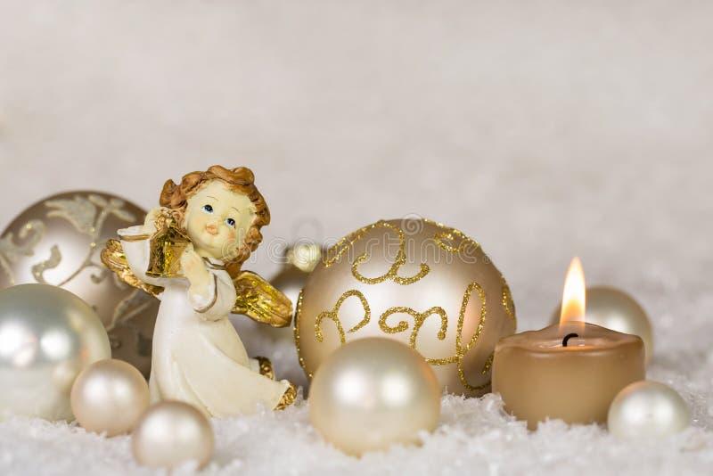 De kaart van de Kerstmisgroet met engel en de kaars in goud, verzilveren stock foto