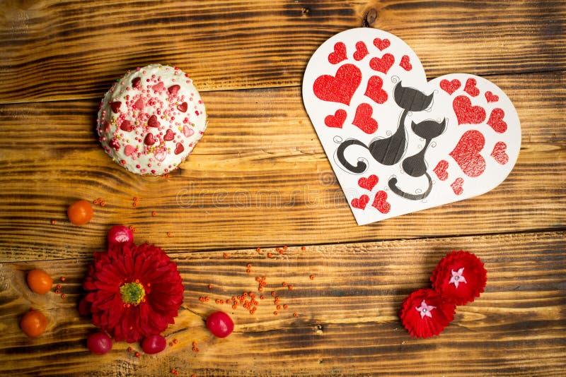 De kaart van de liefdefamilie, suikercake, rode bloemen houten lijst stock afbeelding