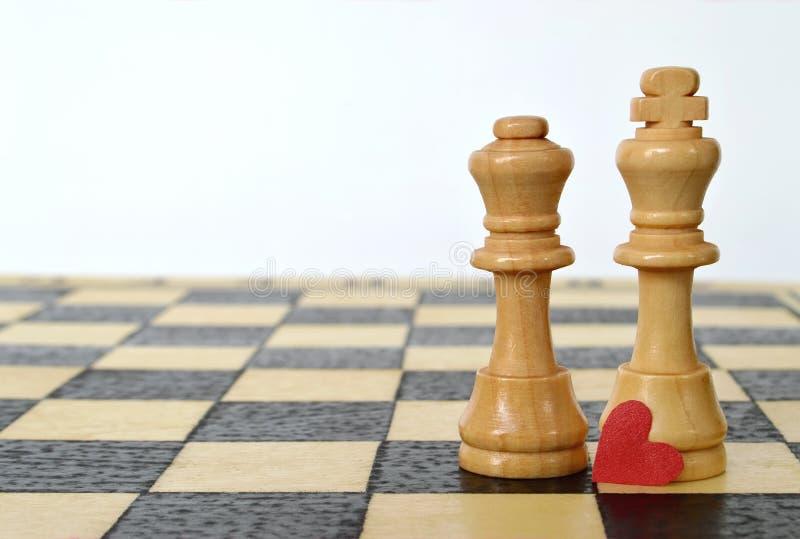 De kaart van de valentijnskaartendag: Hart, koning en koningin op de schaakraad stock foto's