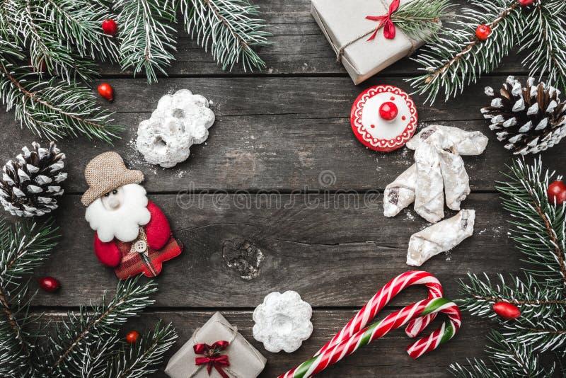 De kaart van de Kerstmisgroet op houten achtergrond, spar vertakt zich, kegels, een sneeuwman, berichtruimte, foelie, snoepjes stock fotografie