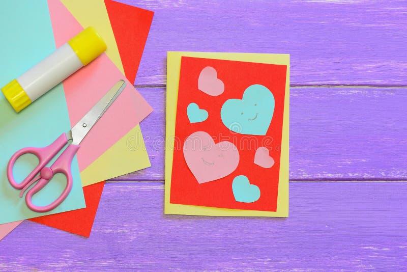 De kaart van de valentijnskaartendag met document harten, schaar, lijmstok, kleurde document bladen op een houten achtergrond Cre royalty-vrije stock afbeeldingen