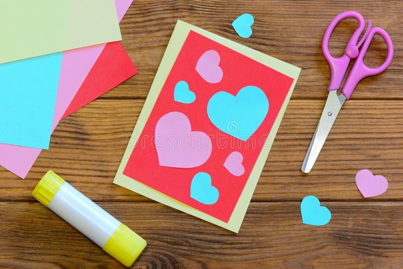 De kaart van de de Valentijnskaartendag van Nice met document harten, schaar, lijmstok, kleurde document bladen op een houten ach royalty-vrije stock foto's