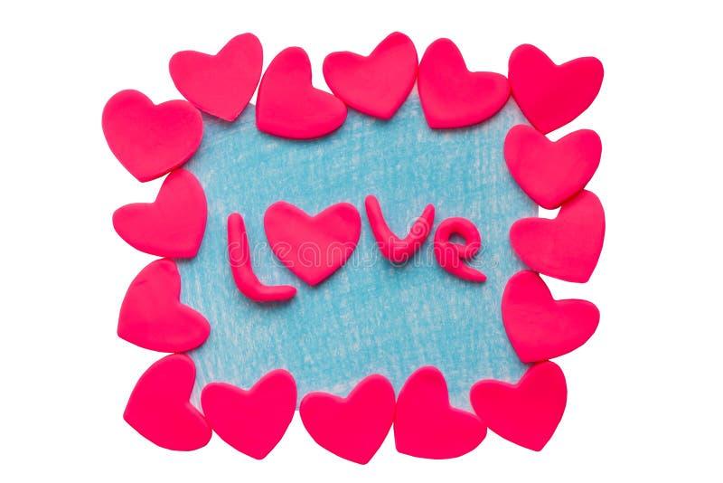 De kaart van Valentine met kleiharten en het woord houden van op een witte achtergrond stock foto