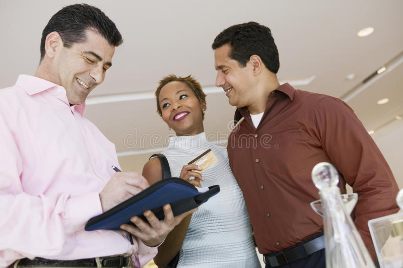 De Kaart van verkopersCalculating Bill While Couple Holding Credit in Opslag stock afbeeldingen