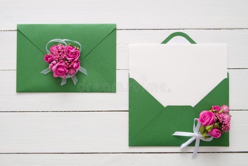 De kaarten of de Valentijnskaartendagbrieven van de huwelijksuitnodiging in groene die enveloppen met roze roze bloemen worden ve stock afbeelding