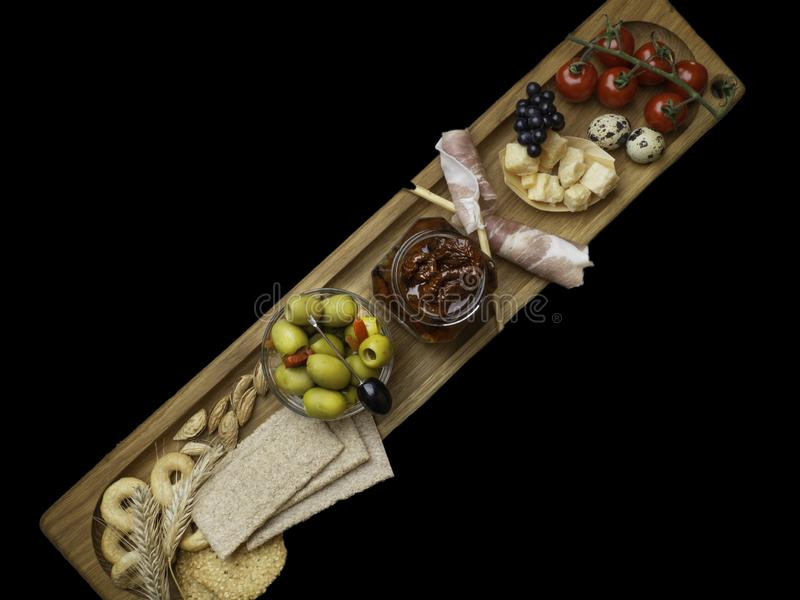 De kaas, prosciutto verpakte broodstokken, eieren, noten, droge en verse tomaten, groene olijven, graangewassen, koekjes op houte stock foto