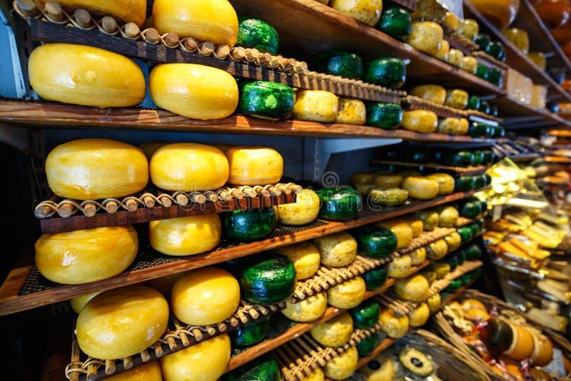 De kaas rijdt groene en gele kleuren op houten planken bij kaasmakerijwinkel stock fotografie