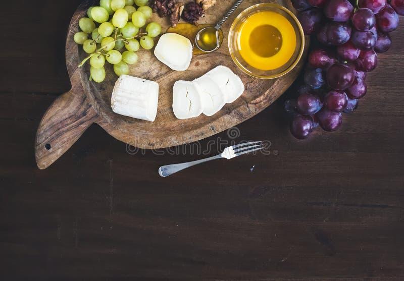 De kaas van de geitbrie met verse greapes en honing op een houten plattelander royalty-vrije stock afbeelding