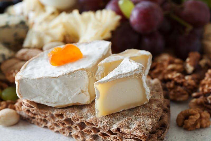 De kaasplaat met druiven, jam wordt gediend, genas meloen, crackers die en royalty-vrije stock foto's