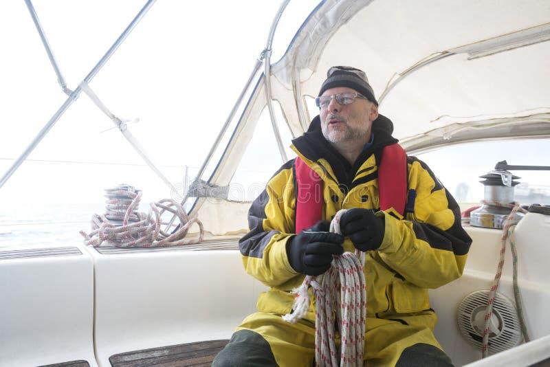De Kabel van de mensenholding terwijl het Zitten op Jacht stock foto's