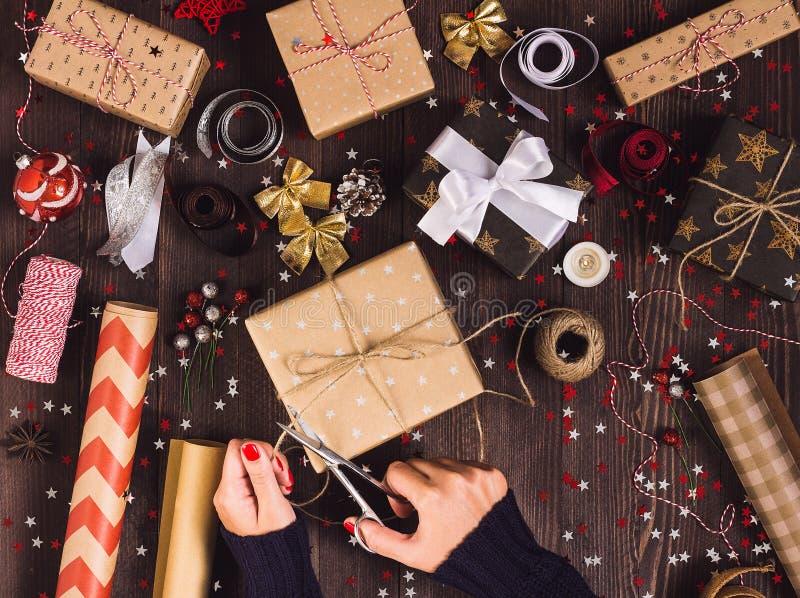 De kabel van de de holdingsstreng van de vrouwenhand met schaar voor het snijden van en de verpakking van de doos van de Kerstmis royalty-vrije stock foto's