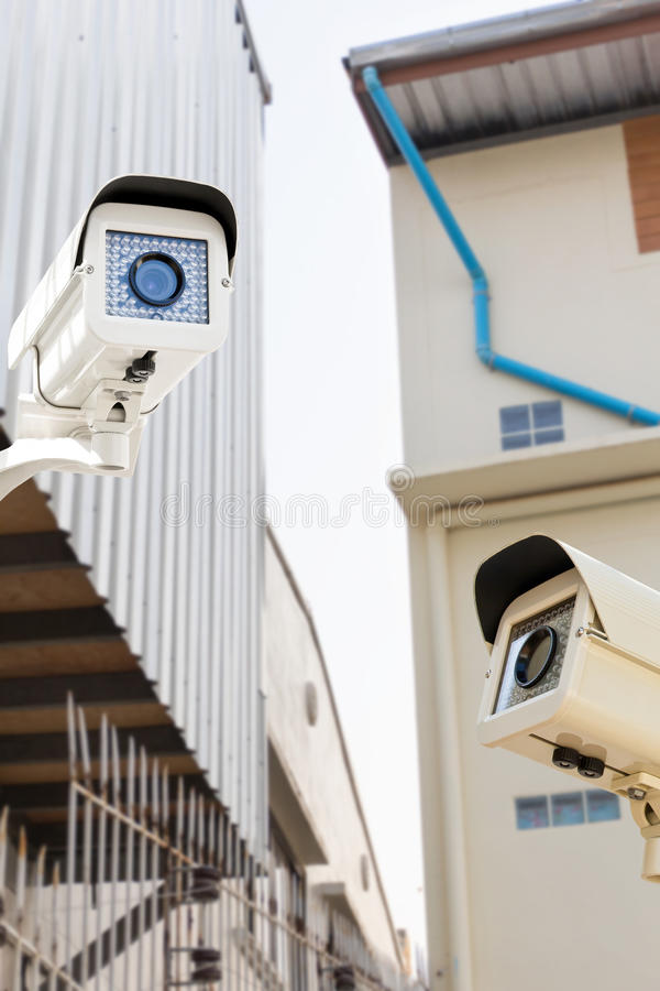 De kabeltelevisie-Veiligheidscamera die op het huis van het binnenplaatsdakwerk werken royalty-vrije stock afbeeldingen