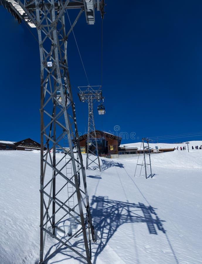 De kabelwagen van de gondellift met toren en post over sneeuw van bergalpen, transpotation van grindelwald aan Eerste piek stock fotografie