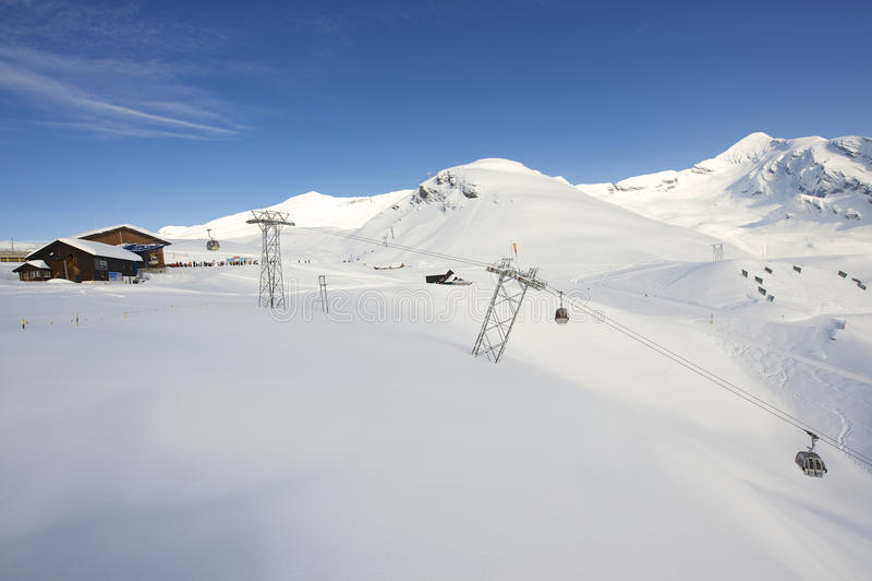 De kabelwagengondels bewegen bergop skiërs bij de skitoevlucht in Grindelwald, Zwitserland royalty-vrije stock foto