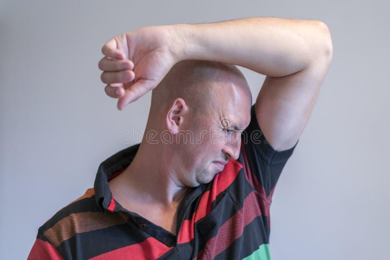 De kale mens, die snuivend zijn oksel, iets stinkt slecht ruiken op grijze achtergrond royalty-vrije stock afbeeldingen