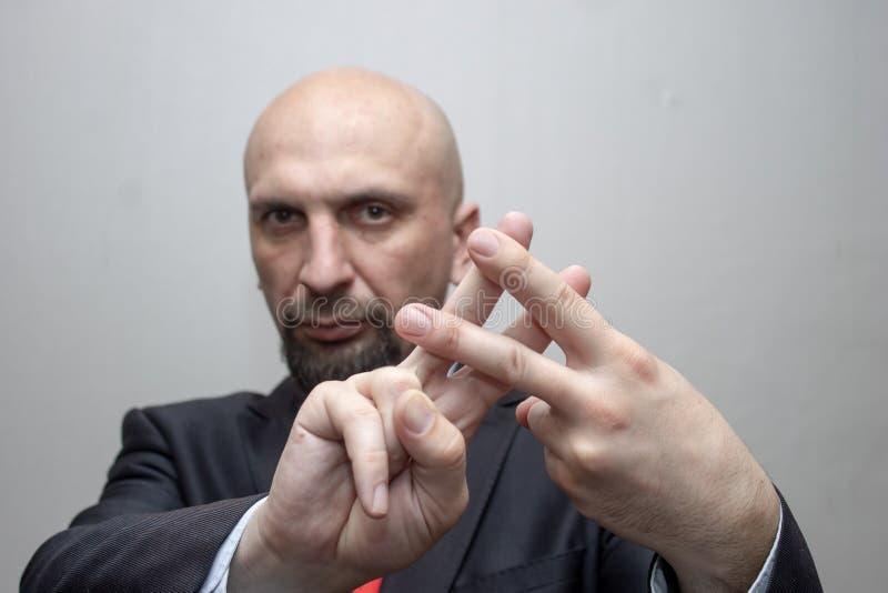 De kale mens in een kostuum toont het teken van de vingersrooster, hashtag, muzikale scherp, onder ogen ziend opsluiting stock afbeelding