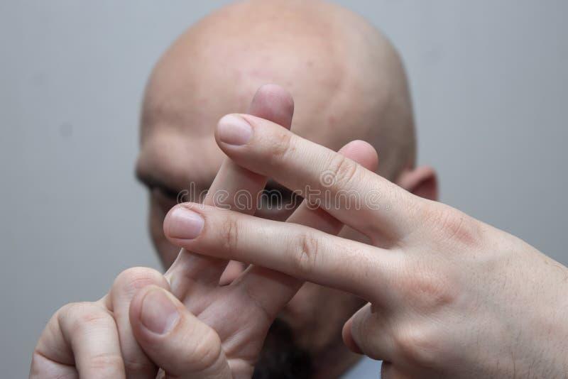 De kale mens in een kostuum toont vingers Roosterteken, hashtag, scherpe musical stock afbeeldingen