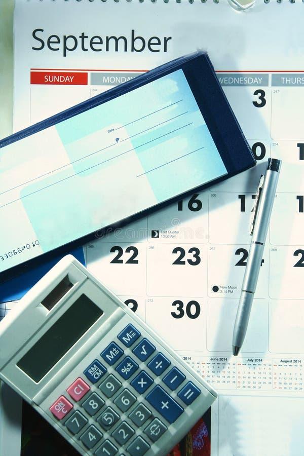 De kalender, checkbook, de calculator en a ballpen royalty-vrije stock afbeeldingen