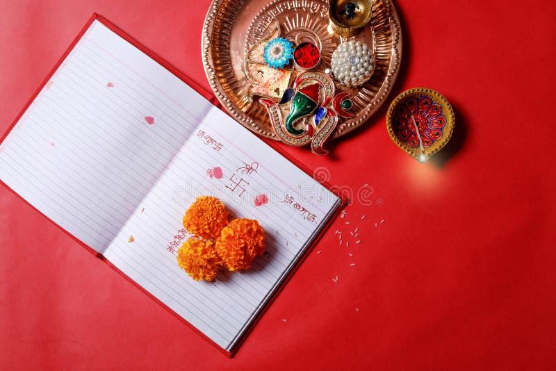 De kalligrafie die in hindi Shubha Labh schrijven betekent Goedheid & Rijkdom, over het Rode boek van de boekhoudingsnota, diya, stock fotografie