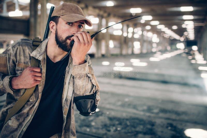 De kalme en stille vechter in eenvormig spreekt in draagbare radio Er is een geweer dat over juiste schouder hangt stock afbeeldingen