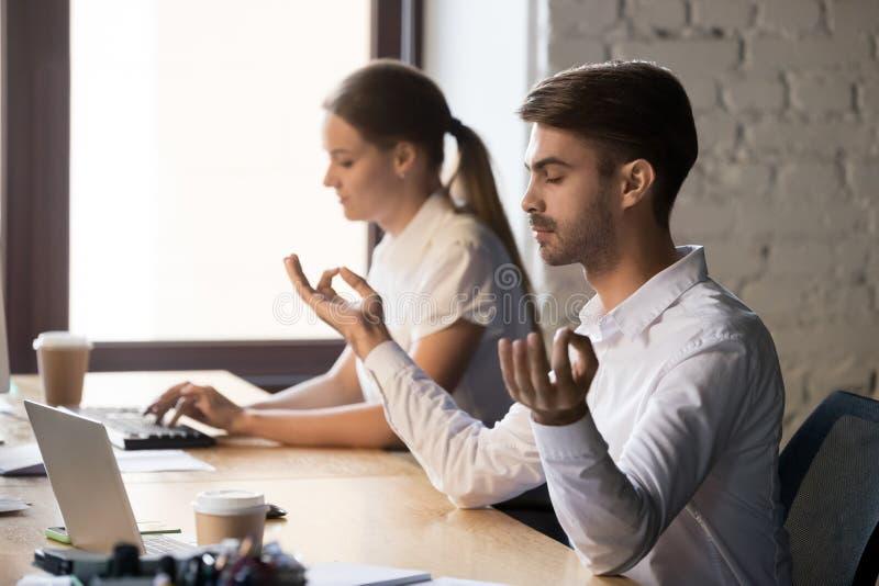 De kalme mannelijke werknemer zit dichtbij computer die op het werk mediteren stock foto